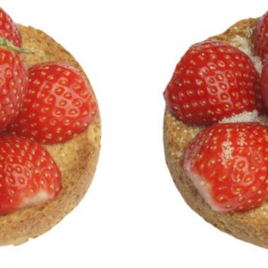 Two whole grain rusks with a thin layer of butter and strawberries